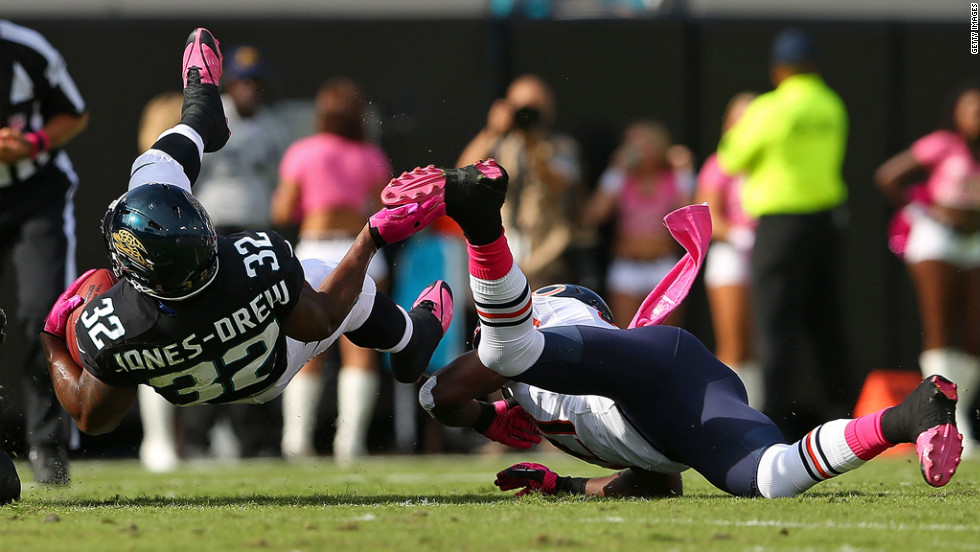 Maurice Jones-Drew of the Jacksonville Jaguars gets tripped up by  Major Wright of the Chicago Bears.