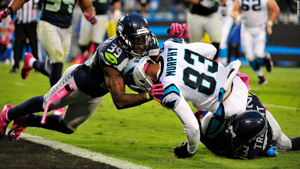 Brandon Browner, left, and Marcus Trufant of the Seahawks tackle Louis Murphy of the Panthers just short of the goal line Sunday.