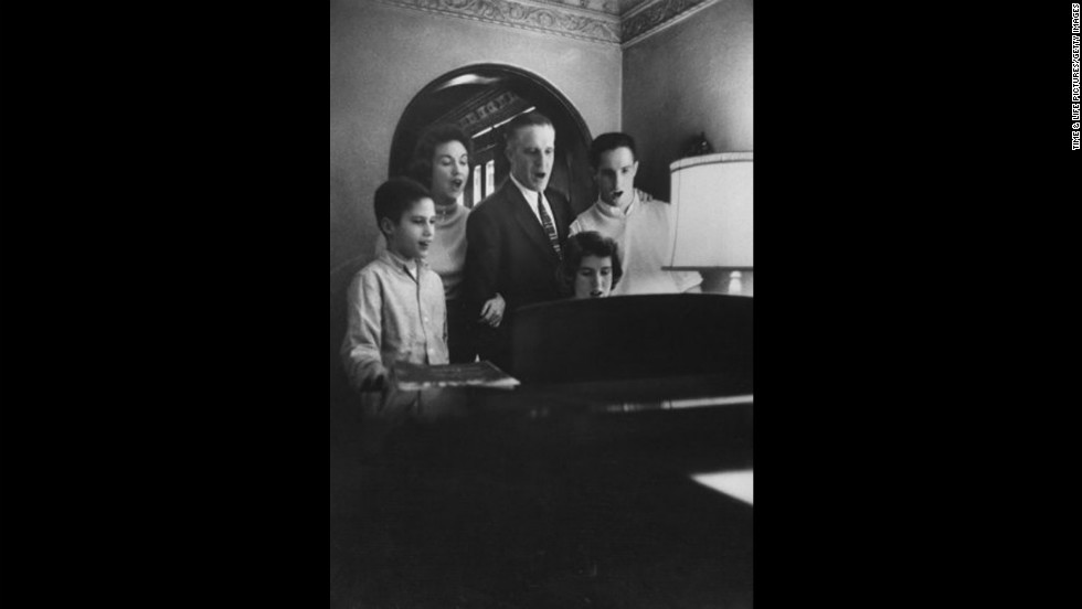 The Romney family, from left, Mitt, mother Lenore, father George, sister Jane and brother Scott get together at the piano for a hymn in 1958. Mitt Romney grew up in a Mormon household.
