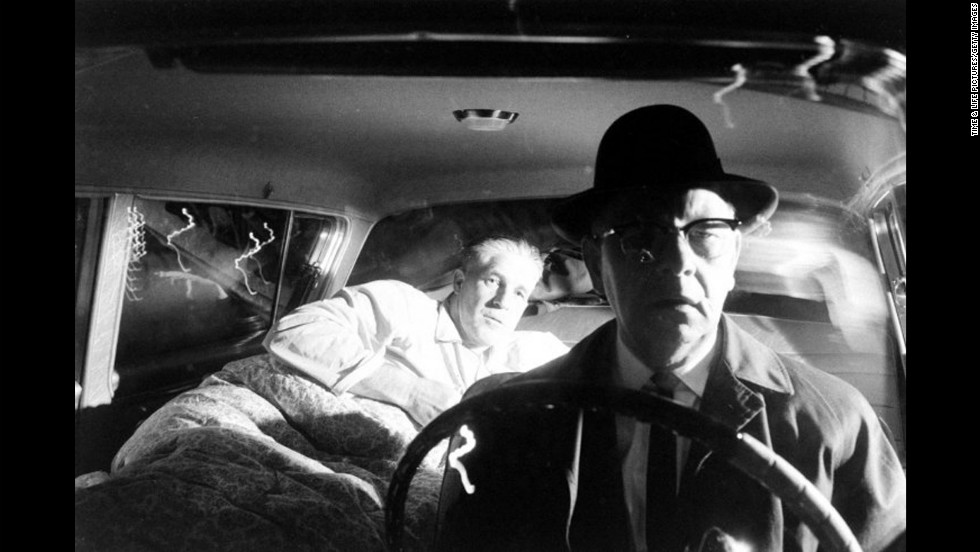 George Romney gets ready to sleep in the back of his car as a chauffeur drives home to Bloomfield Hills, Michigan, after a long day of work on a new state constitution and a quick change into pajamas in 1962. Mitt Romney's father was elected governor of Michigan that year.