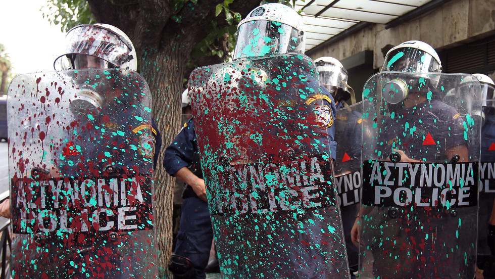 Riot police are covered with paint thrown by protesters.