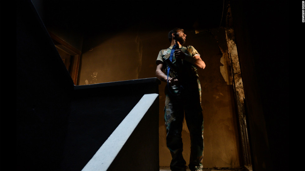 A Syrian rebel fighter takes position inside a house in Aleppo during clashes with government forces on Tuesday.