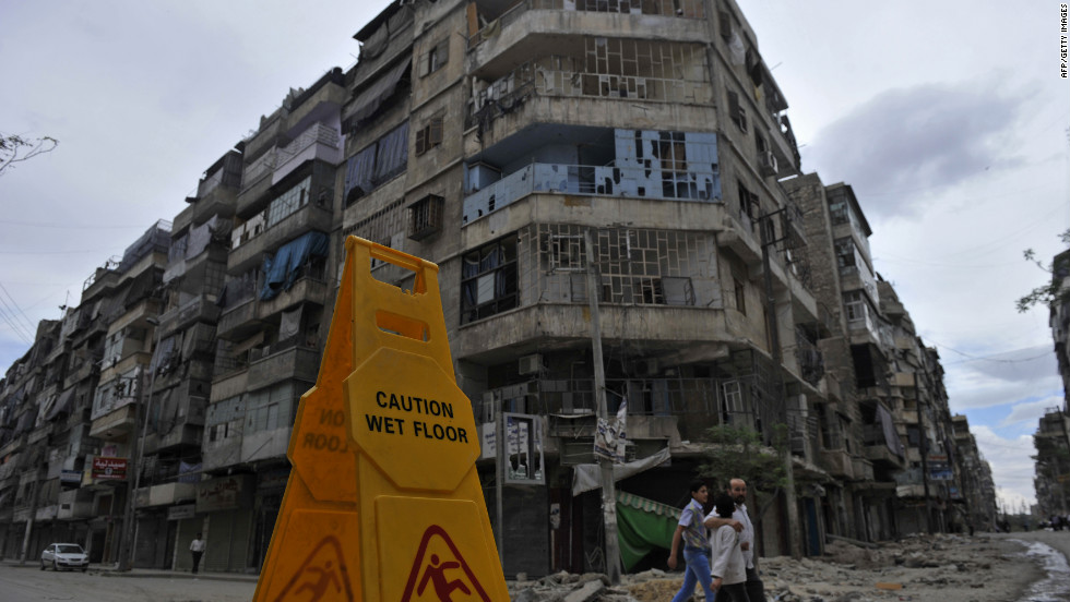 Syrian civilians walk in front of damaged buildings in Aleppo on Thursday.