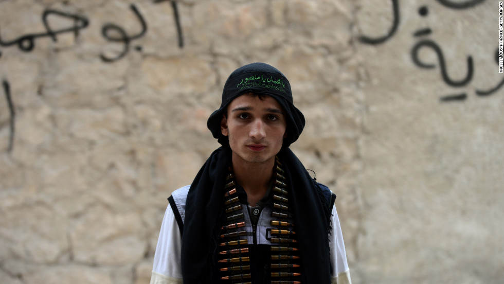 A Syrian opposition fighter stands near a post in Aleppo on October 11, 2012.