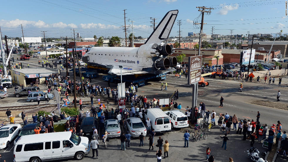Endeavour moves down a main road lined with onlookers. Endeavour was flown cross-country atop NASA's Shuttle Carrier Aircraft from Kennedy Space Center in Florida to LAX on September 21.