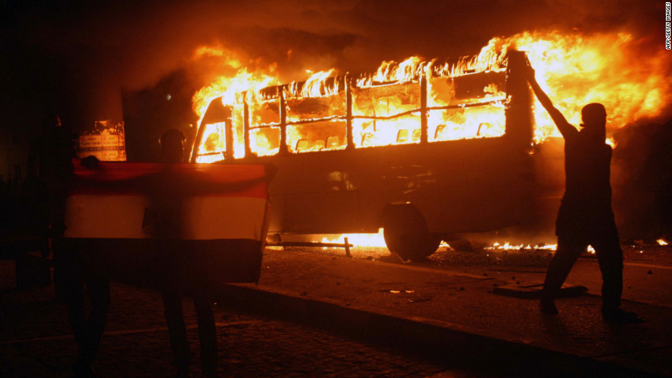 Egyptian protesters hold a national flag as they walk past a burning bus.