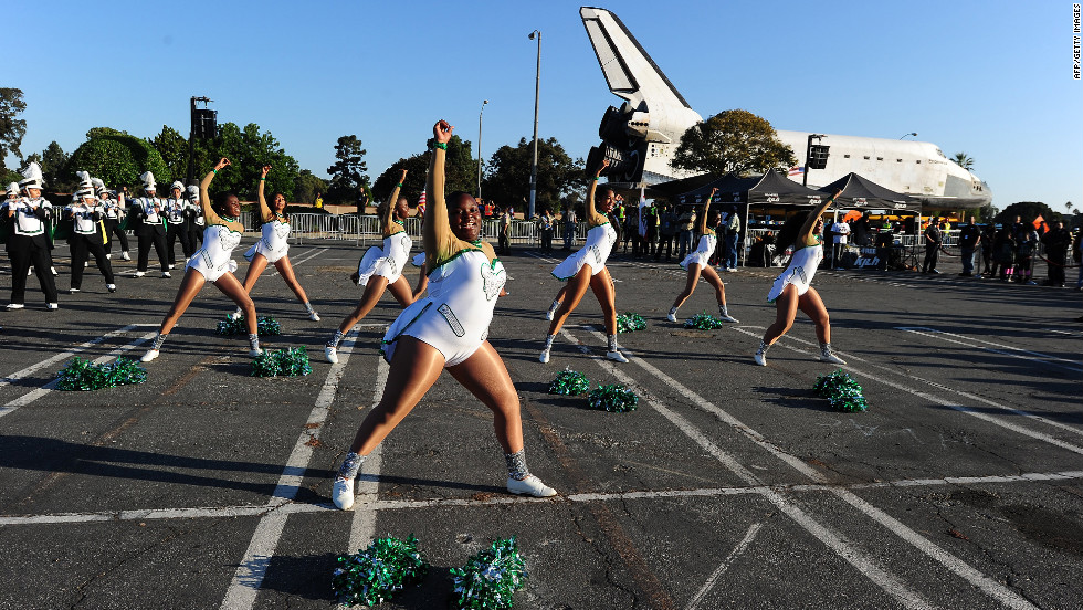 Inglewood High School cheerleaders perform near the shuttle on Saturday.