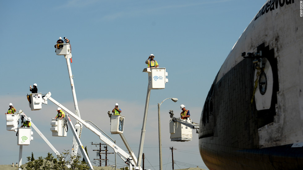People take photos from cherry pickers Saturday as the shuttle moves along Crenshaw Drive in Inglewood, California.