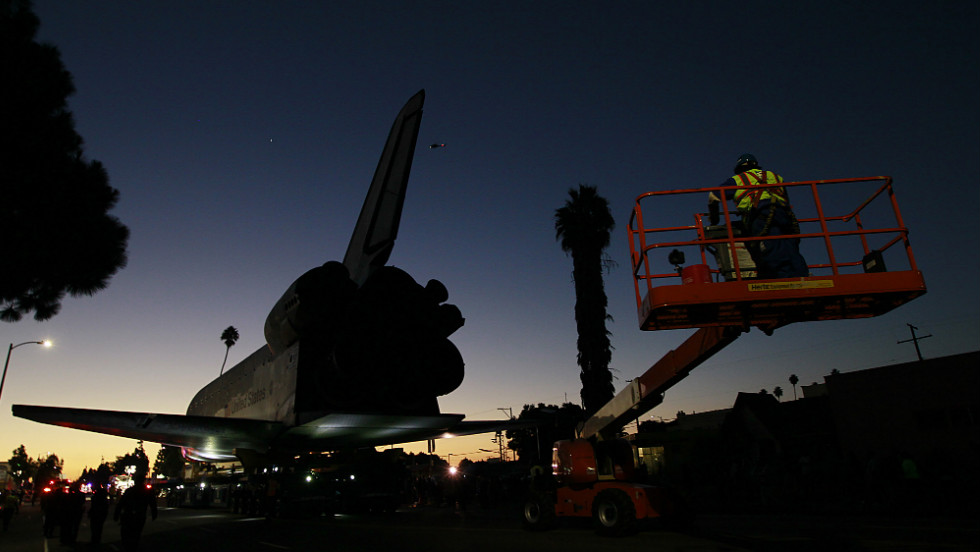The sun rises as the space shuttle Endeavour slowly moves along Martin Luther King Boulevard to the California Science Center on Sunday.