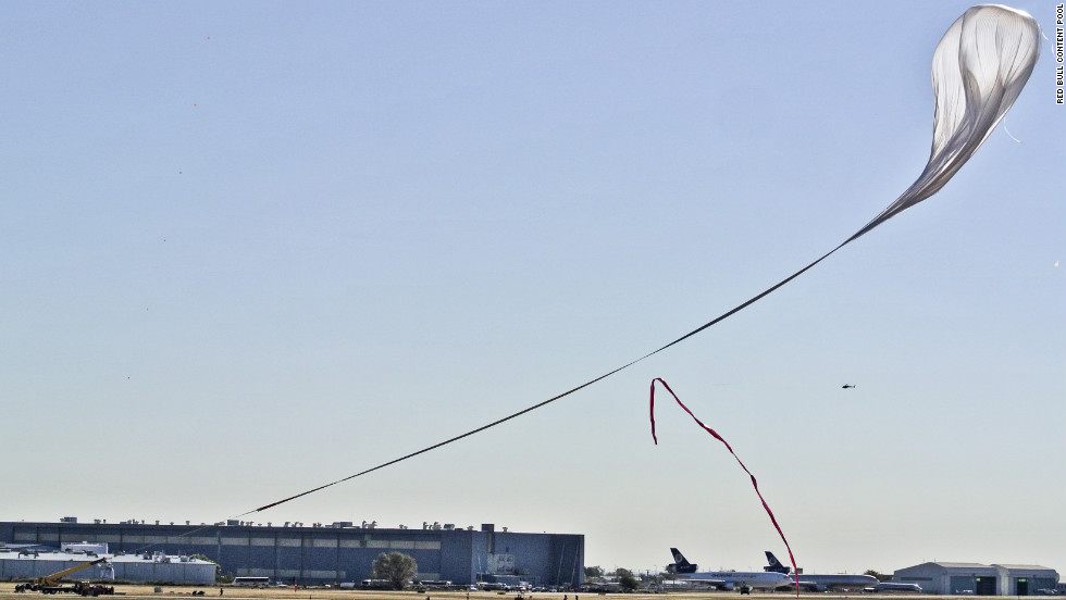 A crane carrying the capsule follows the helium balloon during the launch on Sunday.