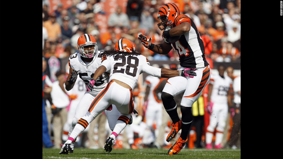 Jermaine Gresham of Cincinnati catches a touchdown pass as he avoids tackles by Cleveland defenders on Sunday.