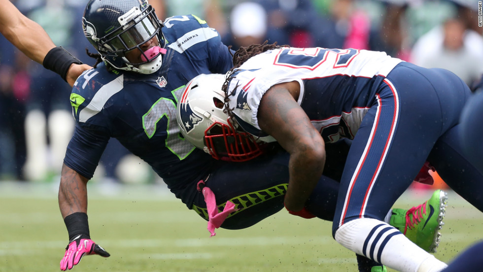 Marshawn Lynch of the Seahawks is tackled by Brandon Spikes of the Patriots.