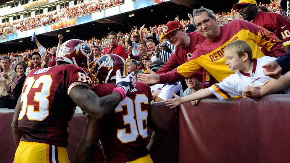 Fred Davis, left, and Darrel Young of the Washington Redskins celebrate with fans after Young scored a touchdown against the Minnesota Vikings.