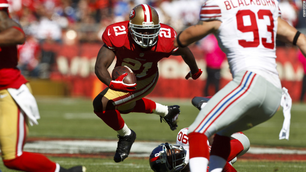 Frank Gore of the San Francisco 49ers breaks a tackle Sunday against the New York Giants at Candlestick Park in San Francisco.