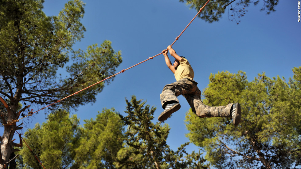 A young fighter climbs along a rope as he trains at a Free Syrian Army camp in Syria's northwestern province of Idlib on Monday.