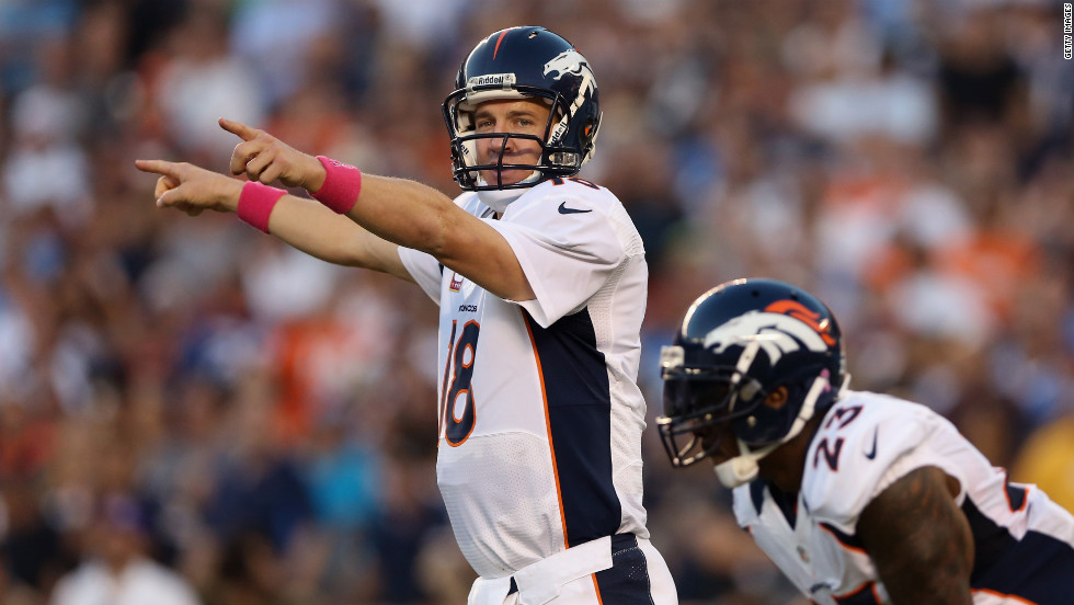 Quarterback Peyton Manning of the Broncos calls out a play next to running back Willis McGahee.