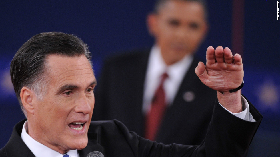 Romney gestures to make a point as President Obama looks on.