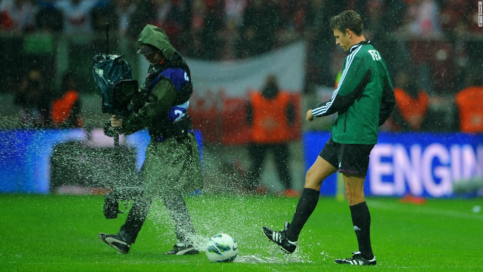 Match referee Gianluca Rocchi tests out the sodden turf but any thoughts of play were soon abandoned with the ball refusing to roll.
