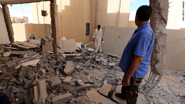 Libyan men inspect a destroyed building in Bani Walid, about 115 miles southeast of Tripoli, last week.
