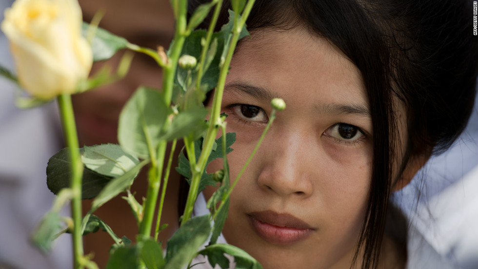 A young woman holds flowers as she waits for the convoy bearing the body of King Sihanouk to drive past in front of the Royal Palace in Phnom Penh on Wednesday.