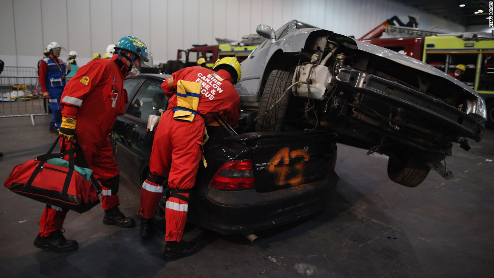 Two cars sit stacked on top of each other as members of the Fire Brigade attempt to reach inside.