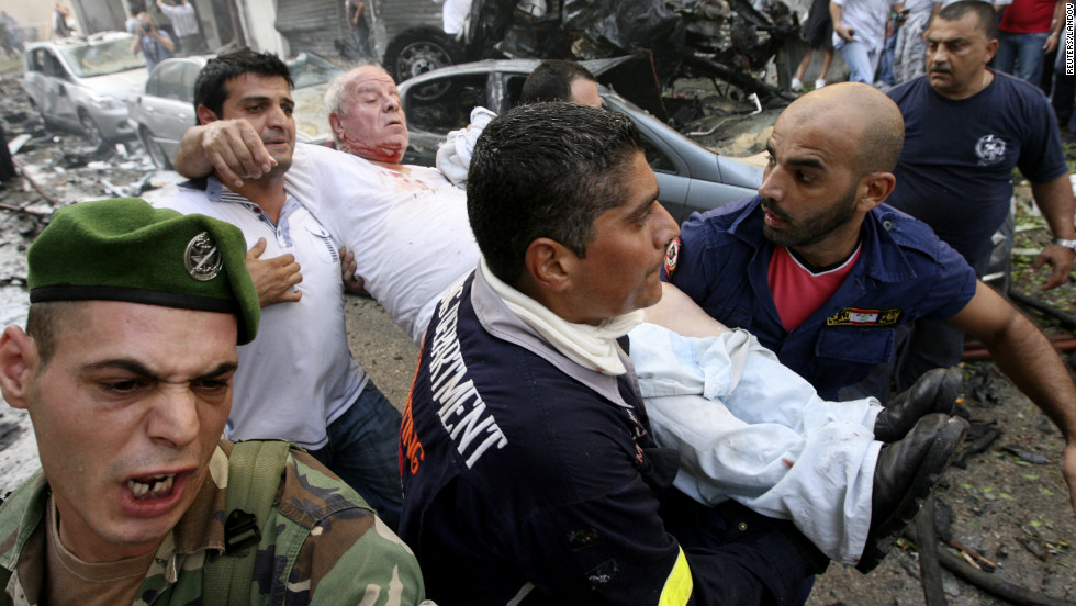 Civil defense members help a wounded man in the immediate aftermath.