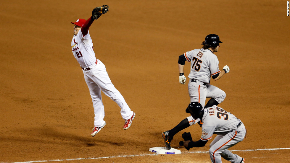 No. 21 first baseman Allen Craig of the Cardinals has to leave the bag to field a throw as No. 75 Barry Zito of the Giants reaches first safely on an RBI bunt single in the fourth inning.