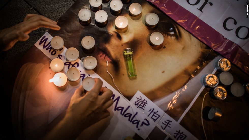 An activist with the Association for the Advancement of Feminism lights candles during a vigil in Hong Kong on Friday.