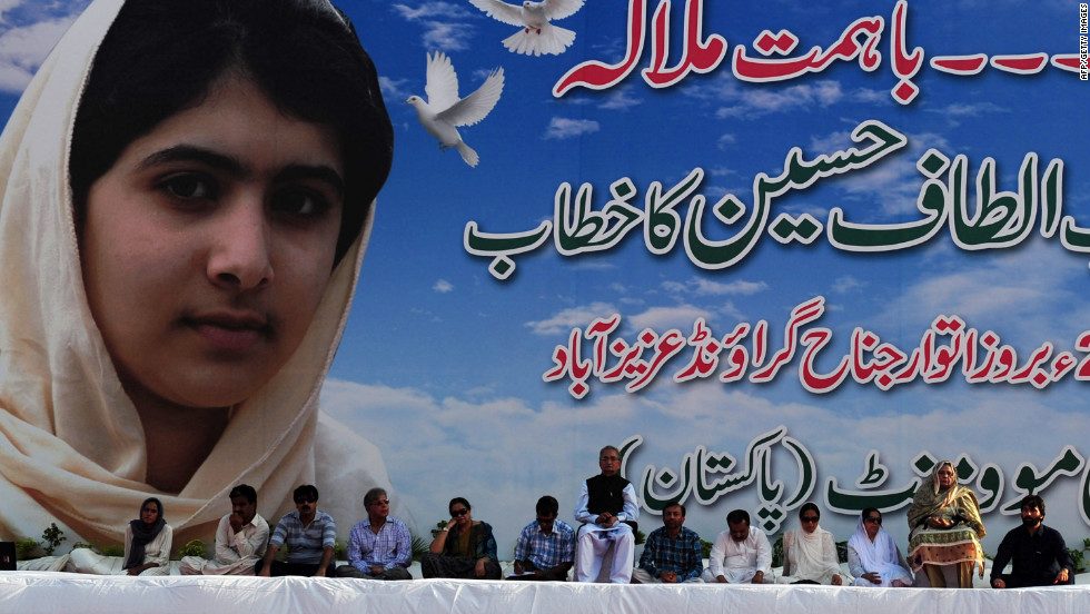 Pakistani leaders of the movement sit in front of a poster of Malala at a procession in Karachi.