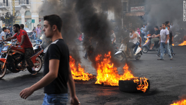 Protesters gather on motorbikes at a road block of burning tires in the northern Lebanese city of Tripoli, on October 20, 2012.