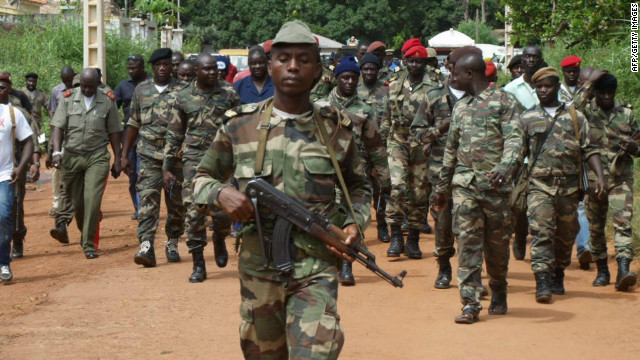 Guinea-Bissau soldiers walk along a street after gunmen raided an army barracks in the capital Bissau on October 21, 2012.