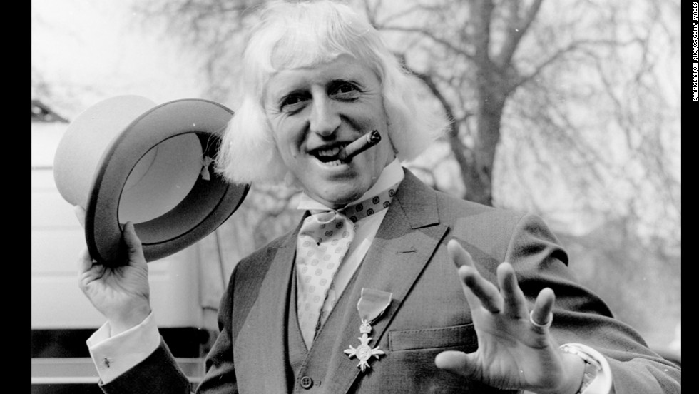 British radio disc jockey, television star and charity fund-raiser Sir Jimmy Savile poses for a photo at Buckingham Palace, London, after receiving the Order of the British Empire in 1972. Since his death a year ago at age 84, Savile has been knocked off his perch as a national treasure, accused of being a predatory pedophile who used his fame and position to abuse youngsters, sometimes on BBC premises.