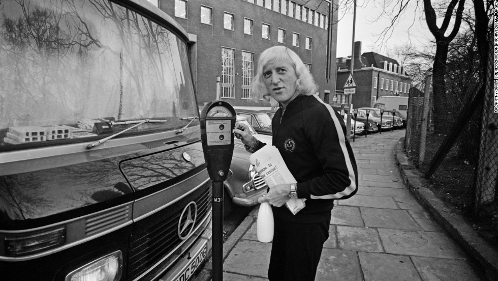 Savile stands on the sidewalk with his motor home.