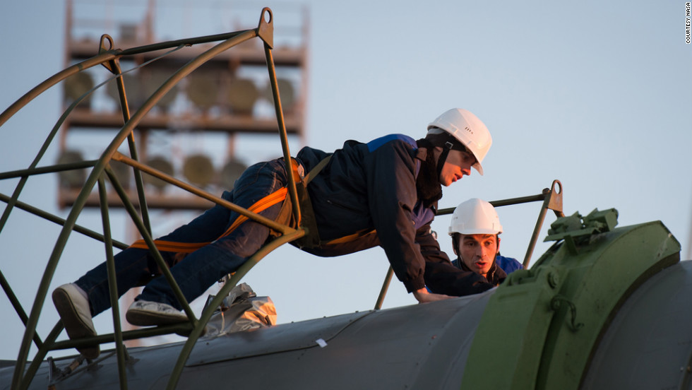Technicians prepare the Soyuz rocket to be erected Sunday at the launch pad.