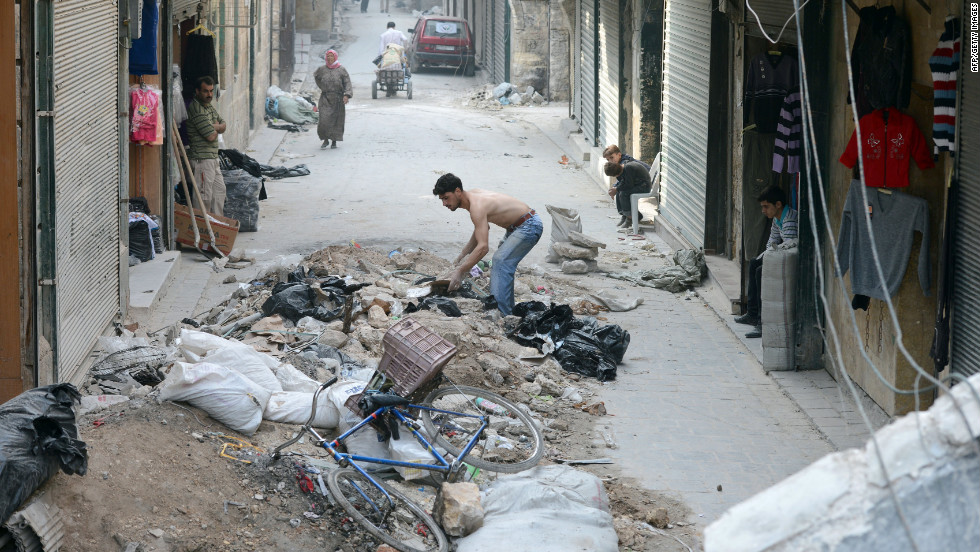 A shopkeeper clears the rubble from in front of his store in the old sector of Aleppo.