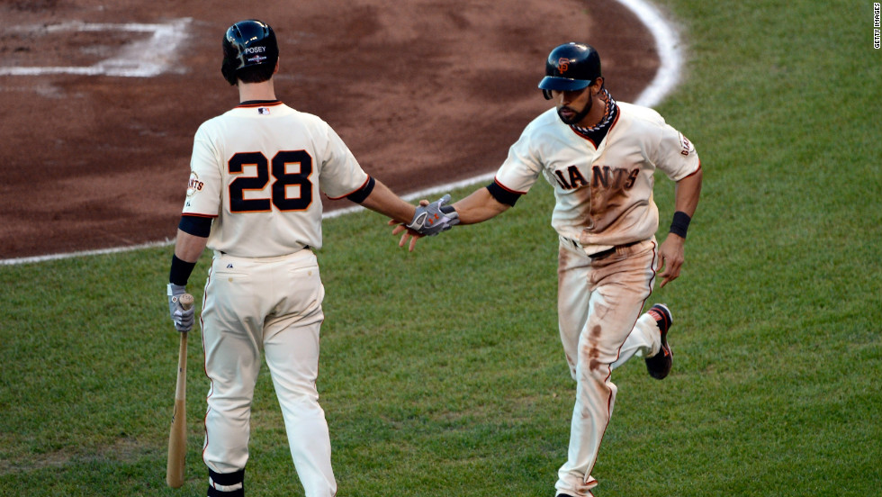 No. 16 Angel Pagan of the Giants gives teammate No. 28 Buster Posey a five after Pagan scores in the first inning.