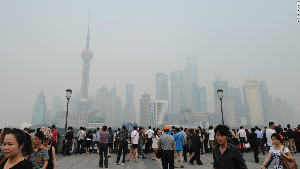 Visitors look out at the skyline clouded by pollution in Shanghai on May 15, 2012.