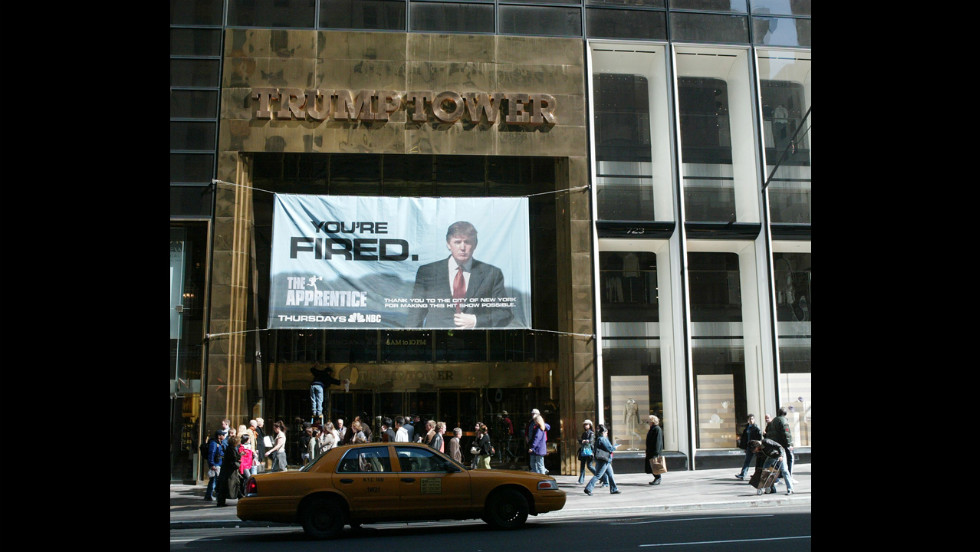 "An advertisement for the television show ""The Apprentice"" hangs at Trump Towers in New York in 2004. The show launched in January of that year. In January 2008, the show returned as ""Celebrity Apprentice."""