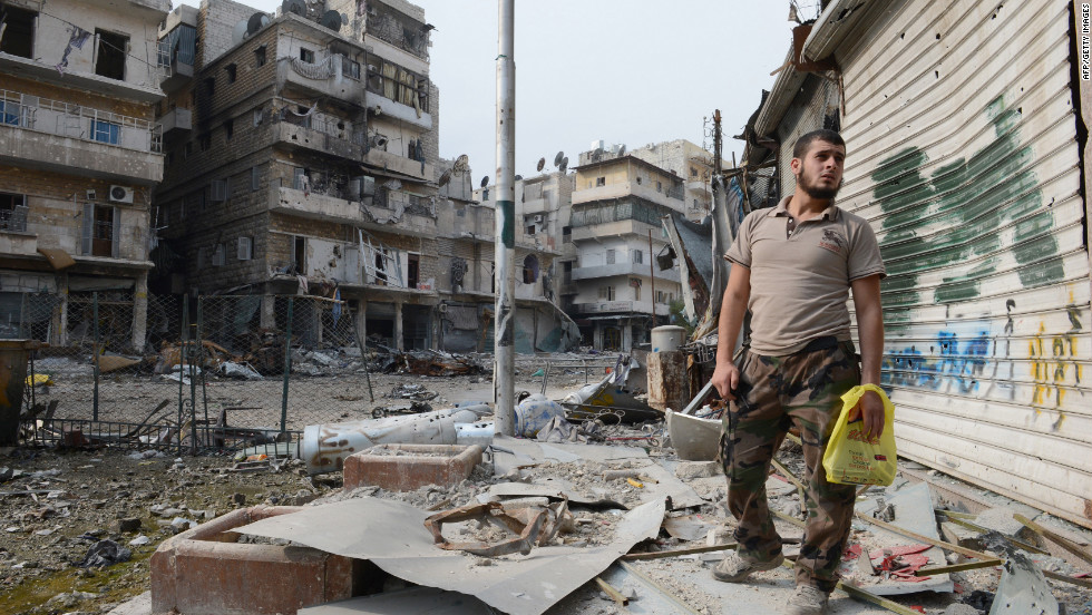 A rebel fighter looks towards the crossroads, destroyed during fighting between government and rebel forces, in the Salaheddin district of  Aleppo, Syria on October 23.