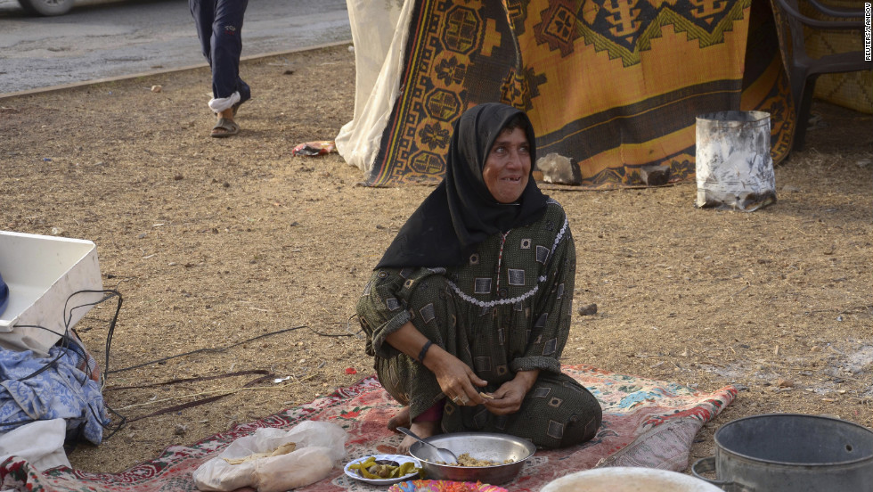 A Syrian woman, displaced by the ongoing violence and living along a street in Aleppo, on Tuesday, October 23.
