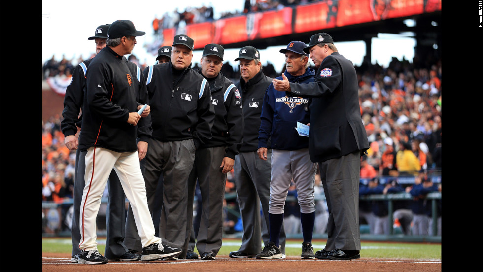 Manager Bruce Bochy, left, of the San Francisco Giants, and manager Jim Leyland, right, of the Detroit Tigers, go over ground rules with the umpires prior to the game.