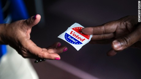 """A poll worker hands out """"I Voted Today"""" stickers during the first day of early voting October 22, 2012 in Washington, DC. Citizens of the District of Columbia began early voting today for the November 6th elections which will include the 2012 US Presidential election.  AFP PHOTO/Brendan SMIALOWSKI        (Photo credit should read BRENDAN SMIALOWSKI/AFP/Getty Images)"""