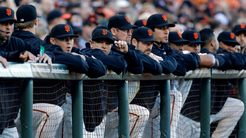 San Francisco Giants players look on from the dugout.