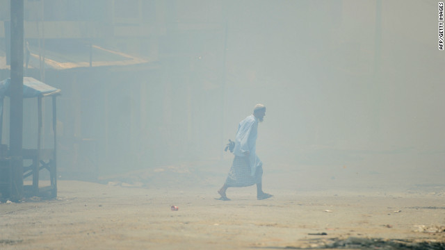 A Muslim walks amid burning houses in Sittwe, capital of Myanmar's western state of Rakhine, on June 12.