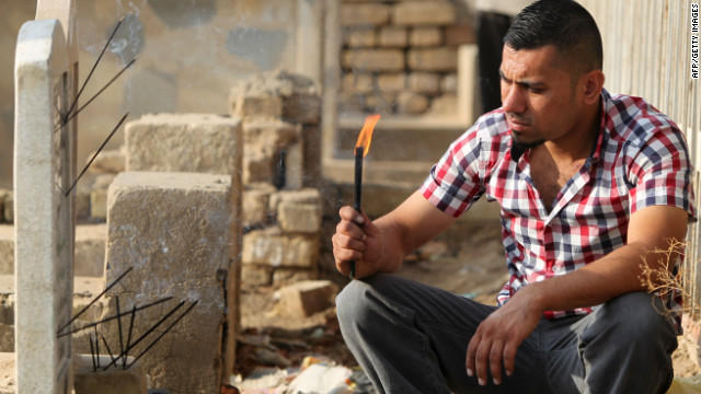 An Iraqi man prays next to a grave in Baghdad on the first day of Eid al-Adha on October 26.