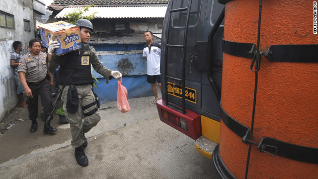 A police officer carries belongings from the house of a suspected militant after a raid in Jakarta on Saturday.