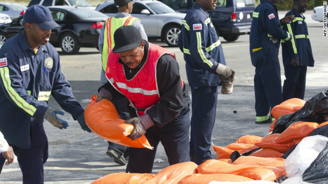 Workers pass sandbags at a distribution center near RFK Stadium in Washington on Saturday.