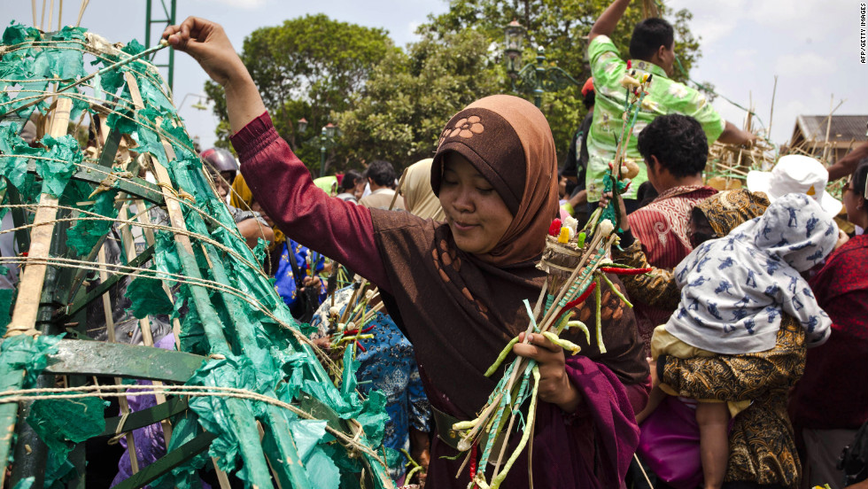A Javanese woman picks vegetables from the Gunungan, a structure in the shape of a mountain, during the Grebeg ritual as part of celebrations for Eid al-Adha on Friday in Yogyakarta, Indonesia. People offer vegetables, peppers, eggs, and other items at the Grand Mosque and receive part of the Gunungan to be blessed in the year ahead.