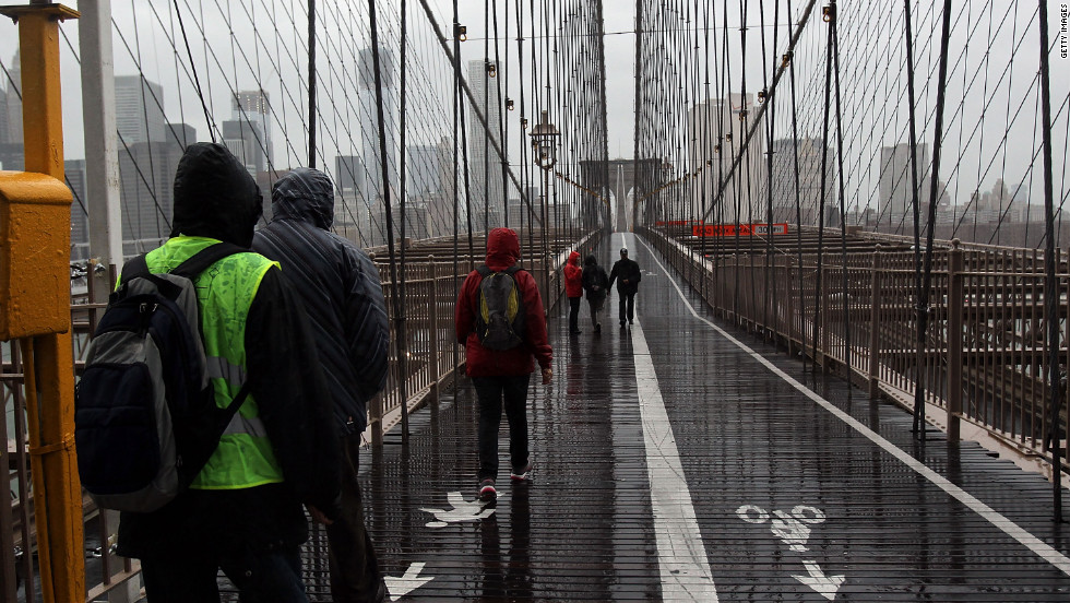 People walk across a rainy Brooklyn Bridge as New York City braces for Hurricane Sandy's arrival.
