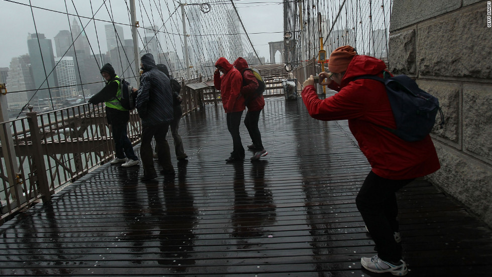 People pose for pictures on the Brooklyn Bridge on Monday.